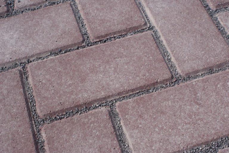Bovenaanzicht van betonklinkers met nokken en gevulde groeven voor toepassing in waterpasserende bestrating